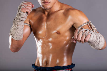 kick: Muay Thai, a male oily body act dress in Thai traditional boxing