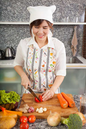 cooking salad, an Asian girl cooking salad in the kitchen slice tomato photo