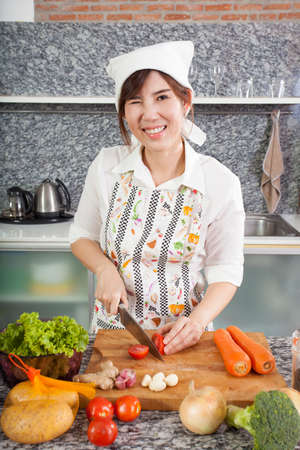 cooking salad, an Asian girl cooking salad in the kitchen slice carrot photo