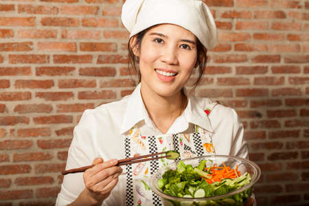 cooking salad, an Asian girl cooking salad in the kitchen with chopstick photo