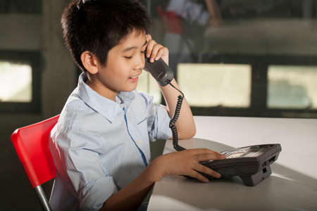wired: operator an Asian young boy pose with wired telephone Stock Photo