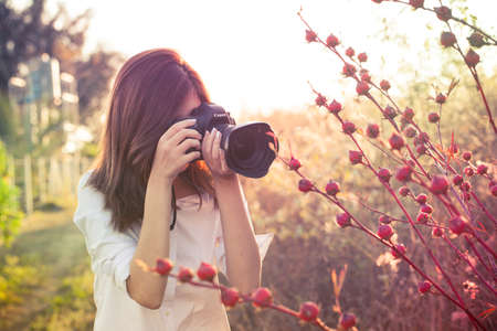 camera girl Thai Asian camera girl shot in natural smiling cute action in the garden and evening sunlight Stock Photo