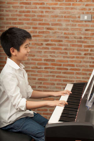 piano lesson Asian boy kid activity playing piano with notes smiling photo