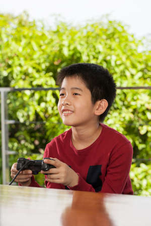 play time: play time an Asian young boy playing with game joystick smiling