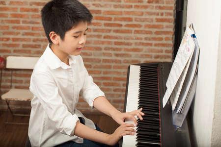 Klavierstunde asiatischer Junge kid Aktivitäten, die Klavier spielt mit Noten lächelnd