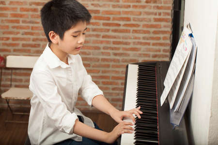keyboard instrument: piano lesson Asian boy kid activity playing piano with notes smiling