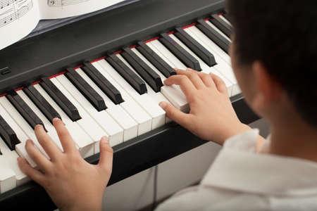 tocando el piano: lección de piano Muchacho asiático actividad niño tocando el piano con las notas sonriendo