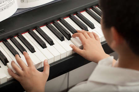 piano: piano lesson Asian boy kid activity playing piano with notes smiling