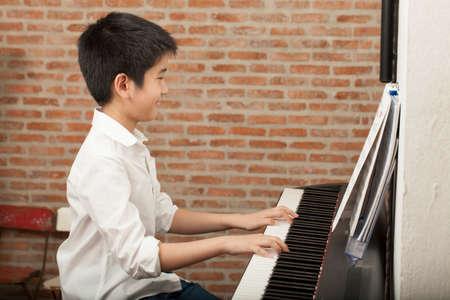 fortepian: lekcja fortepianu Asian Boy dzieciak gra na fortepianie działalność z uśmiechem notatki