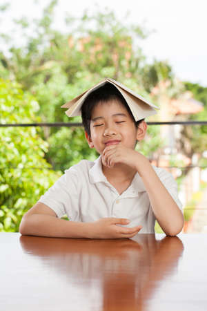 imply: education an Asian young boy put a book on his head imply studying on homework