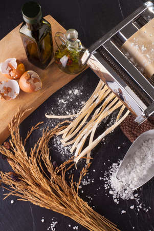 fresh pasta making of homemade fresh pasta tagliatelle with egg and flour overhead angle Stock Photo