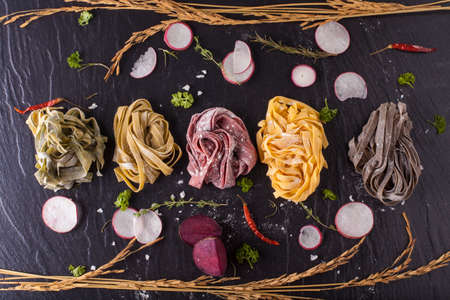 Raw fresh pasta tagliatelle in six color decor with herbs on black stone background