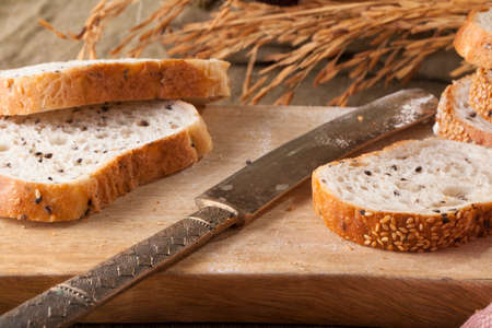 bread knife: Bread, a set of variation of breads on a wood chopping block with bread knife Stock Photo