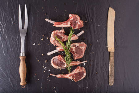 lamb shank: Rack of lamb, Raw rack of lamb cut in pieces decorate and seasoning with rosemary tomato herbs and olive oil fork and knife on black stone
