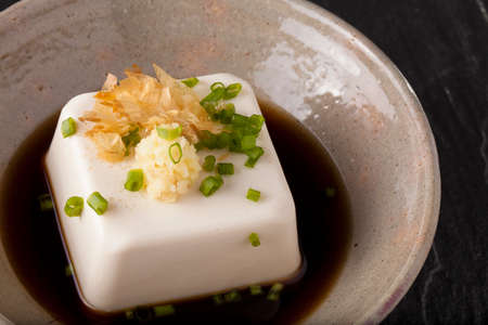 Japanese tofu, Japanese soft cold tofu with sauce in a dish on dining table Stock Photo