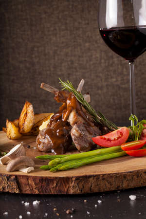 lamb shank: Rack of lamb steak, Rack of lamb steak cut in pieces decorate and seasoning with vegetable and herbs and red wine serve on chopping wood block