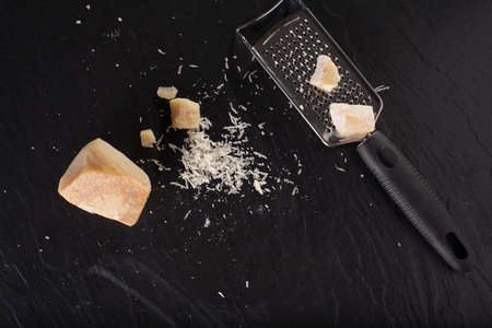 grater: grated cheese, grated parmesan cheese with a grater Stock Photo