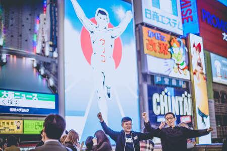 OSAKA, JAPAN - NOVEMBER 5, 2015 : Osaka at night, Showing tourism in Osaka attraction at night acting fun for photo shoot, Osaka, Japan 新闻类图片