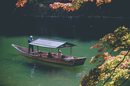 paddler: 6 Nov 2015, ARASHIYAMA, KYOTO Prefecture, JAPAN, Local boat with a paddler rowing in Katsura green River among red maple tree leaf in Autumn season Editorial