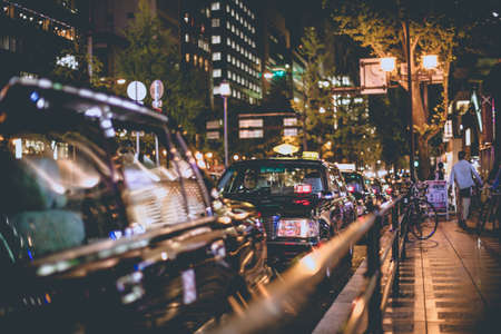 night shift: Osaka, Japan - 7 NOV 2015 Night shift Black taxi line up in queue in the city centre Osaka, Japan Editorial