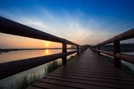 water  panoramic: Long road on the wooden bridge by the lake with silhouette of dramatic colour sunrise sky, Thailand