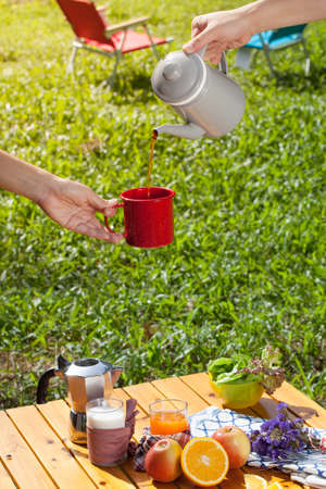 picnic food: hand gesture pouring coffee from a jar to a glass over picnic table with various fruits, juice, pancake, coffee  at the camping area. Stock Photo
