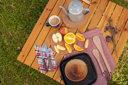 campsite: picnic, view of picnic table with various fruits, juice, pancake, coffee  at the camping area. Stock Photo