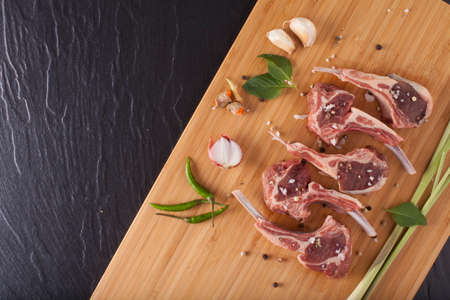 Raw rack of lamb cut in pieces seasoning salt herbs and pepper decorate on black stone and brown bamboo wood background .