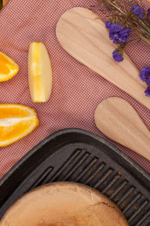 steel pan: Wood made spatula and pancake on a steel pan put on decorated table with fruit and flower