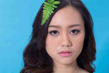 covergirl: beauty face of teenage Asian girl wearing light make-up with fern leaf on her hair