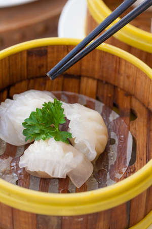 Chinese steamed white dumpling or Hakau Dim sum stuffed with minced shrimp decorated in bamboo made steamer local style with chopsticks.