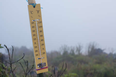 A wooden retro thermometer hanging at the mountain peak showing winter season, Chiangdao , Thailand Stock Photo