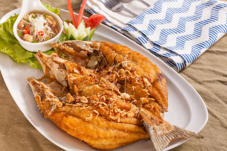 A dish of brown crispy deep fried whole sea bass fish with Thai style spicy dip sauce.