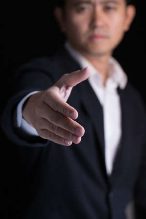 cooperate: A business man wearing black suit giving one hand for shaking in cooperate look. Stock Photo
