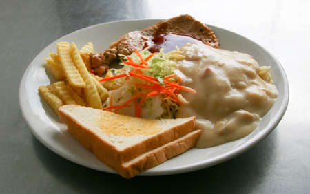 Grilled pork steak and spaghetti white sauce.
