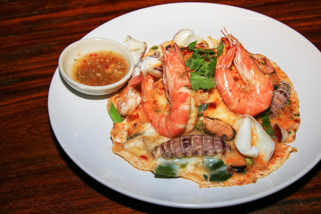 Rice topped with thick egg, Seafood Tomyum (Thai food).