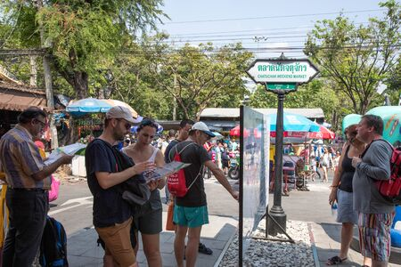 BANGKOK, THAILAND - February 23, 2019 : Tourist couple use their map to determine direction and point in the way they wish to go at Chatuchak weekend market.