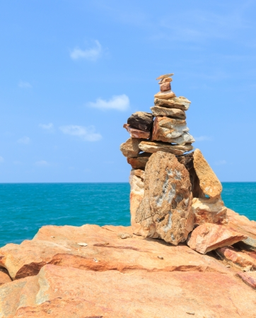 Stack of stones and blue sky on the sea photo