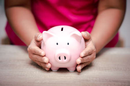 Woman hand holding pink piggy bank for saving money prepare financial management in the future, concept business saving money and investment growth professional.