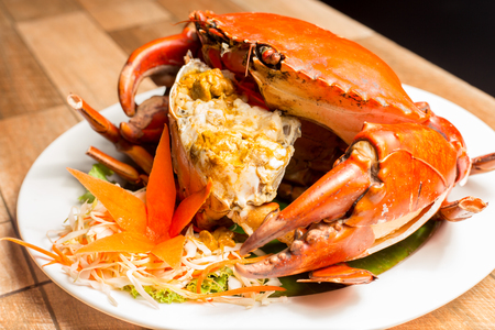 Steamed crab or Boiled crab fresh with crab's spawn in white dish showing the delicious crab's eggs inside its shell on wood table. Thai seafood.