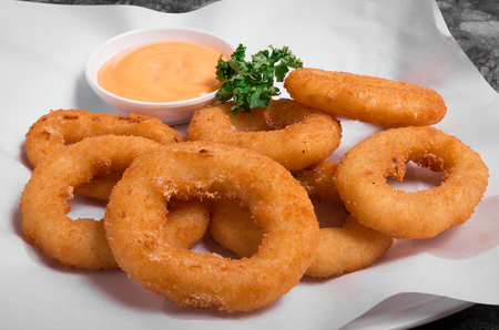 Plate of delicious looking golden onion rings or calamari ring with sauce.