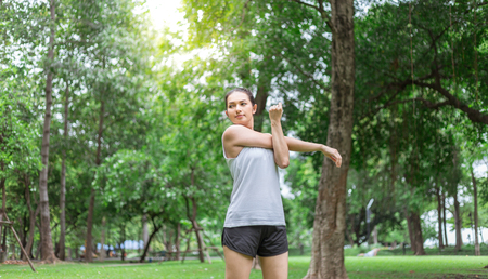 A young woman getting ready for athletic and fitness training outdoors. Healthy lifestyle concept with sunrise early morning.