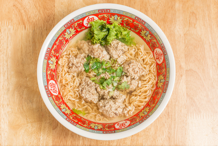 Close up of Instant noodle with meat ball and green Coriander on wood table