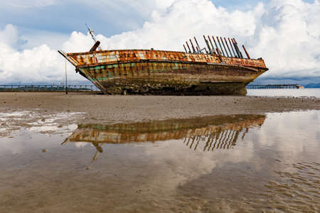 Shipwreck on a Beach with Blue Sky