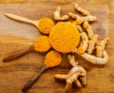 Turmeric roots with turmeric powder on wooden background Stock Photo