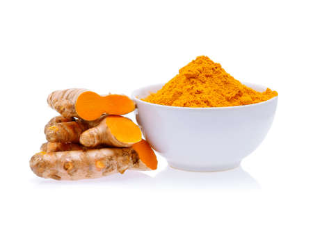 Turmeric roots and turmeric powder in white bowl isolated on white background
