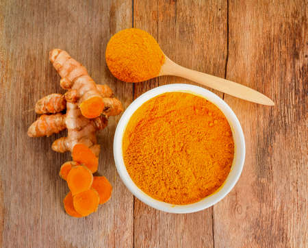 top view Turmeric roots with turmeric powder on wooden background Stock Photo