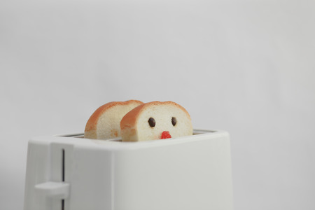 Bread with Cute Face  Decorated by coffee bean as the eyes and strawberry jam as nose  Baking in Toaster  photo