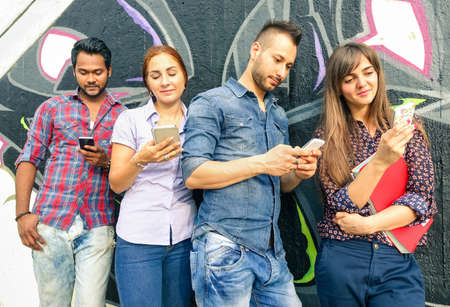 cell phone addiction: Group of friends with mobile sharing sms online - Multiracial students play with cell phone technology addicted - Young hipster people use smartphone - Concept of urban friendship - Graffiti modified Stock Photo