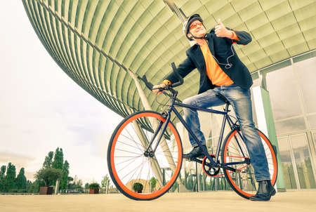 Young hipster business man with bicycle in a urban area - Modern concept of ecological transportation with guy wearing alternative fashion clothes - Vintage nostalgic filtered look - Man with bike